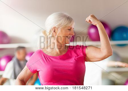 Confident mature woman showing off her bicep