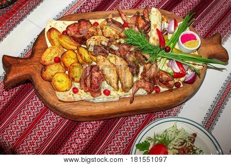 Assorted barbeque plate. Grilled potato and meat platter- beef, pork ribs, quails, chicken fillet served with flatbread, chili pepper, red onion, dill, horseradish and mustard on a large wooden tray.