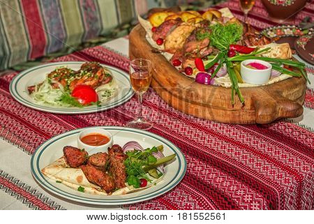 Table served for dinner. Grilled pork served on flatbread with red onion, pickled cucumbers, dill, parsley and sauce with assorted barbeque platter and roasted quail on a plate.