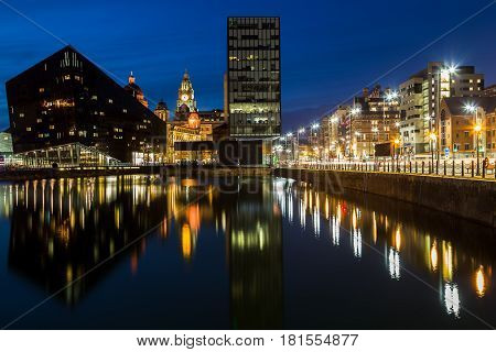 The Mann Island complex reflects off the water of the Canning Dock in Liverpool during twilight.