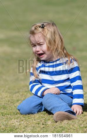 facial emotions. unhappy cute baby boy small little child with long blond hair in blue clothes crying on green grass in park or garden on sunny summer day outdoors on natural background