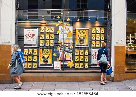 NorwichUnited Kingdom - August 1 2016: A Woman looks at the display in a bookstore window announcing the latest book on the the Harry Potter series
