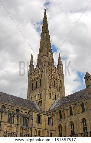 The spire of Norwich Cathedral against a clouds background