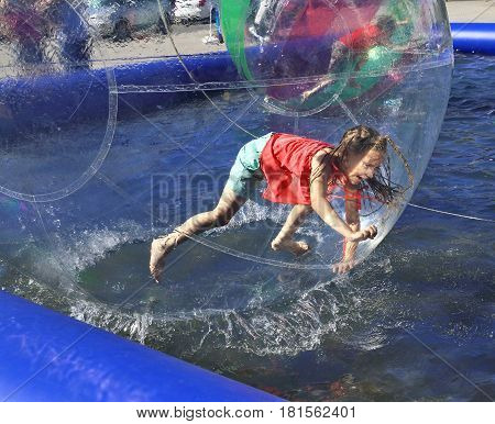 Zorbing. The girl runs inside a transparent sphere