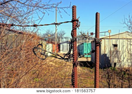 Rusted fittings with barbed wire in fencing