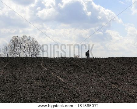 A man with a metal detector on a plowed field, against a background of sky and clouds