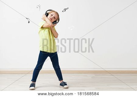 Portrait of pretty Caucasian girl wearing headphones over empty wall background with music notes and copy space.