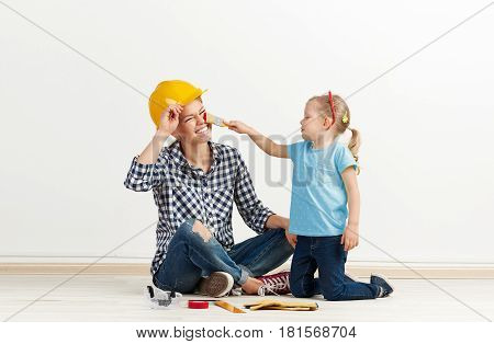 Funny picture of laughing female in protective helmet and little girl with paintbrush. Concept of house remodeling and repair.