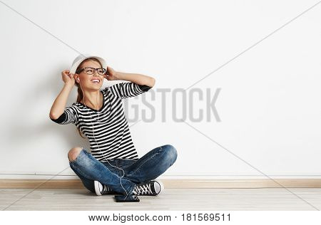 Pretty smiling woman sitting on the floor in earphones with digital tablet pc. Portrait of young happy female listening music over empty wall with space for advert.