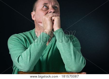 Nice portrait of mature man in greenish-blue shirt looking up with hope