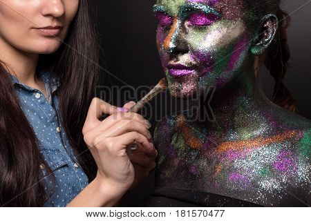 Makeup artist applies black paint and colourful powder on young model. Creative body art on the theme of space and stars. Bodypainting project: art, beauty, fashion