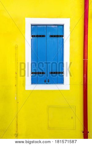 Picturesque complementary colors on blue window on yellow wall of houses on the famous island Burano, Venice, Italy