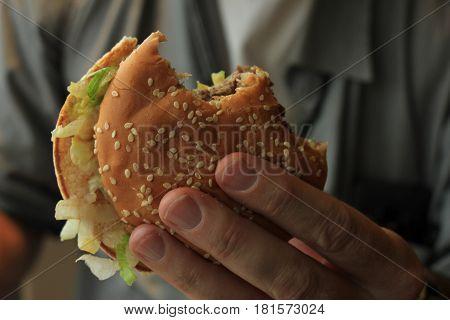 A Man holding a fresh made hamburger