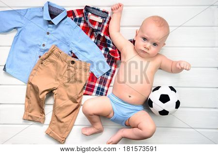 Baby on white wooden background with clothing and football toy. Wish list or shopping overview for pregnancy and baby shower. View from above
