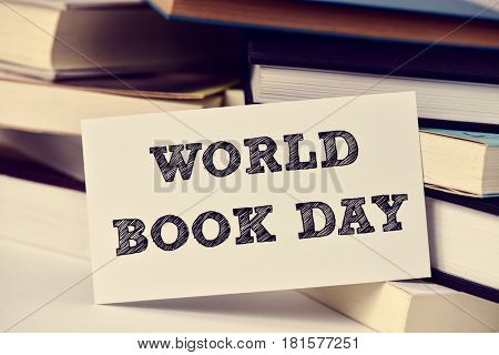 closeup of a piece of paper with the text world book day in front of a pile of books, placed on a white surface