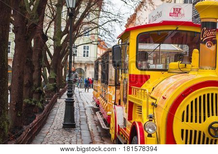 Ukraine Lviv - December 15 2016: Sightseeing road train in the Rynok Square next to Lviv city council expects tourists for a sightseeing tour of the city of Lviv.