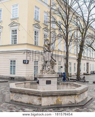 LVIV UKRAINE - February 21 2017: Statue of Adonis at Market Square in Lviv in winter