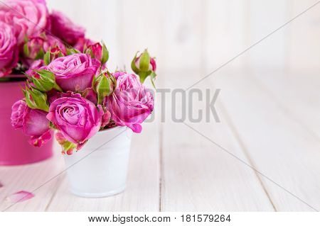 Pink roses(peony) in vase on white wooden background. flowers and