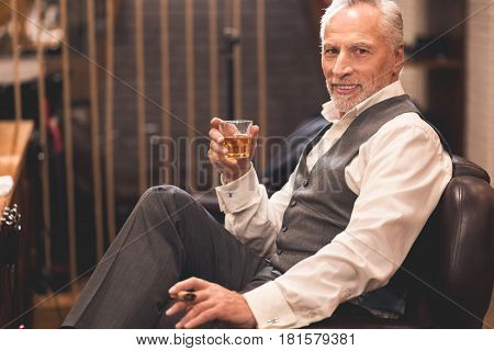 This place worth visiting . Charismatic confident old man sitting in the barbershop and holding cigar and glass of whisky while enjoying free time