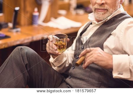 Enjoying expensive life. Charismatic brutal aged man sitting in the barbershop and enjoying cigar and glass of whisky while spending free time