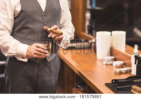 Join me in prosperous lifestyle. Experienced handsome old businessman standing in the barbershop and holding glass of whisky while enjoying the visit