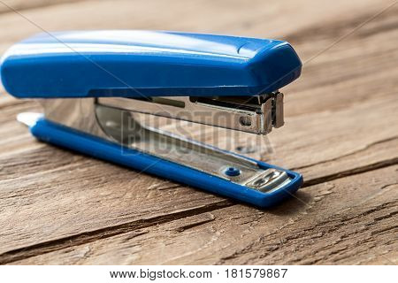 blue stapler on wooden background, close-up isolated