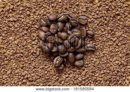 Pile of cofee seeds on instant granulated cofe background top view