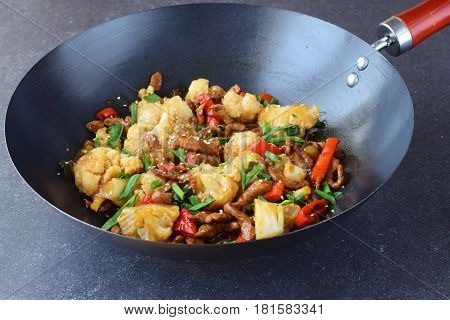 Sweet and sour beef stir fried in the wok with cauliflower and vegetables on a grey abstract background. Oriental dish. Healthy eating concept
