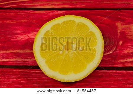 The photo shows a cross section of lemon fruit. Visible juicy pulp. The fruit lies on the base of the boards painted red paint.