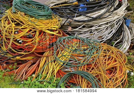 A huge pile of electrical cord in various colors left in a pile on the outside grass