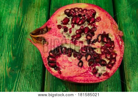 The photo shows a cross-section of pomegranate. Visible juicy pulp and seeds. The fruit is placed on a wooden substrate made of boards painted with green paint.
