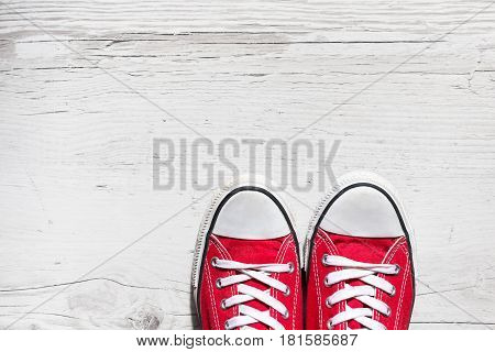 Old red sport shoes on wooden background