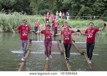 BOVENKARSPEL, THE NETHERLANDS - SEPTEMBER 11,2016: A team athletes running over an obstacle of beams in the water for a survival run for athletes