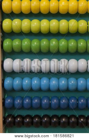 Abacus counting frame. Calculating tool with rainbow colored beads sliding on wires. Used in pre- and in elementary schools as an aid in teaching the numeral system and arithmetic or as toy.