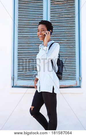 Young Black Woman Walking And Talking On Cell Phone