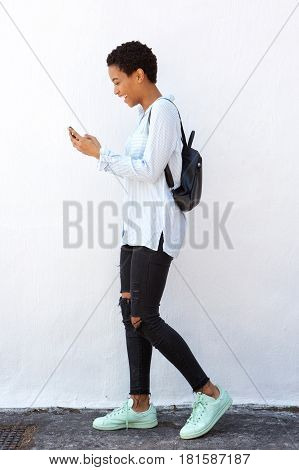 Young African Woman Walking With Mobile Phone And Bag
