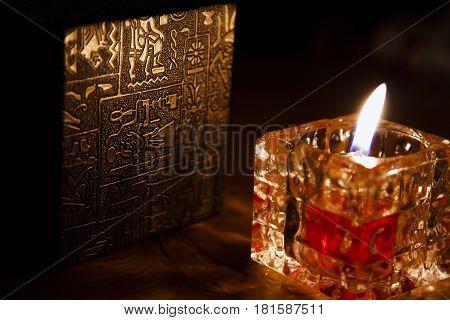 Candle burning in the dark in glass holder on black backgroundrelection on desk