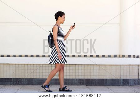 Side Portrait Of Young Woman Walking On With Cellphone And Bag