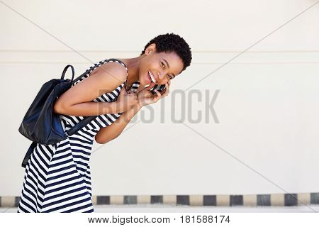 Young African Woman Walking And Laughing With Mobile Phone