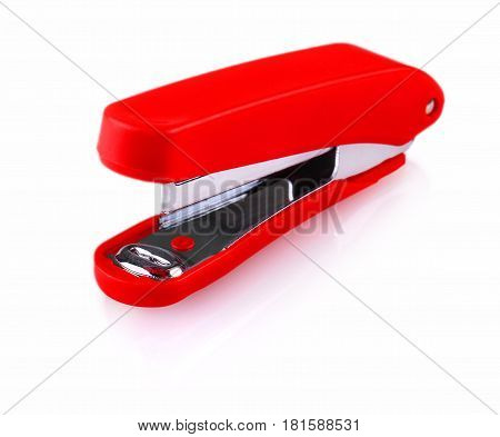 Red office stapler on white background .