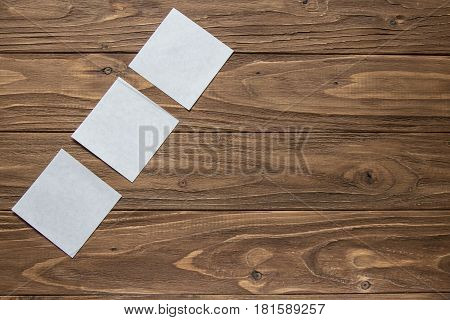 three white square notes, left side on wooden background
