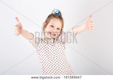 Portrait of little  beautiful and confident girl showing thumbs up isolated on white background
