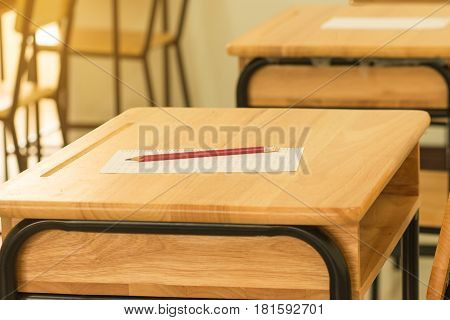 answer sheet test score sheet with red pencil on wood desk in empty classroom