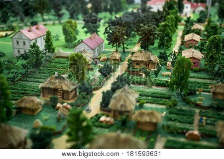 Miniature layout or model or maquette landscape of Ancient countryside or village with small houses, trees, orchards. Selective focus