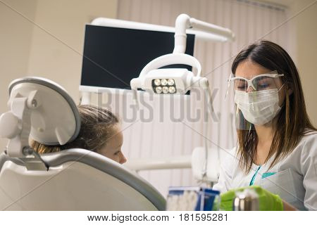 Dentist woman preparing for treatment at dental clinic. She is wearing dental facemask. She has little girl patient.