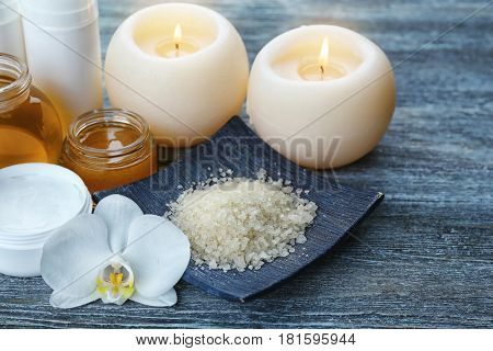 Spa setting with aroma candles, delicious honey and sea salt on grey wooden table