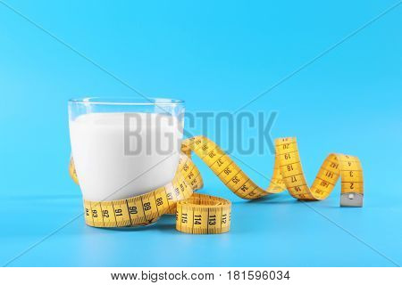 Glass of milk with centimeter on blue background