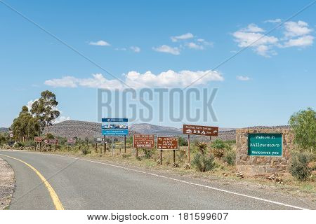 WILLOWMORE SOUTH AFRICA - MARCH 23 2017: A welcome board and many road signs line the entrance road to Willowmore a small town in the Eastern Cape Province