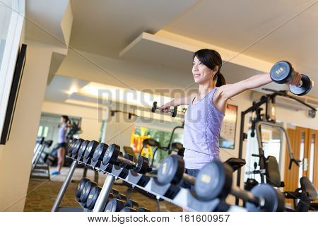 Woman weighting up dumbbell in gym