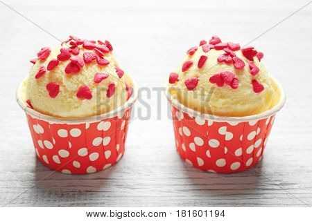Cups with tasty ice cream and sprinkles on wooden table